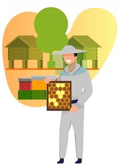 Homem em traje segurando o quadro com favos de mel de abelha.