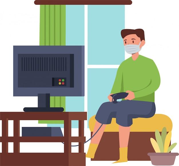 Homem está jogando videogame sozinho em casa enquanto estiver usando máscara médica