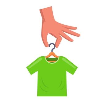 Homem está segurando um cabide com uma camiseta verde. ilustração vetorial plana.