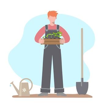 Homem está segurando uma caixa de madeira com mudas. próximo a ele estão ferramentas de jardinagem: uma pá e um regador. vetor