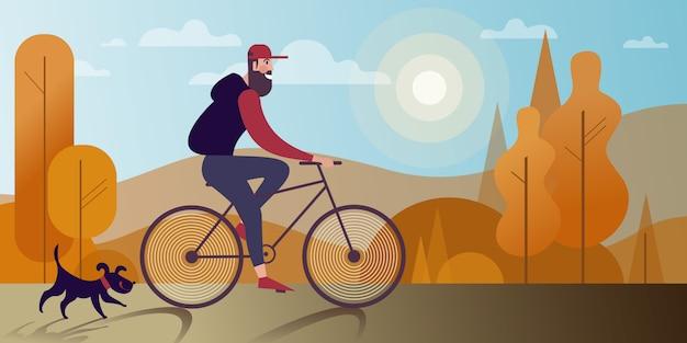 Homem farpado novo que monta uma bicicleta com um cão no parque do outono.