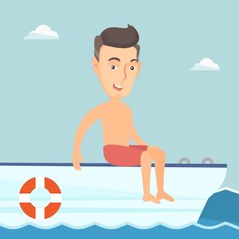 Homem feliz novo que bronzea-se em um veleiro.