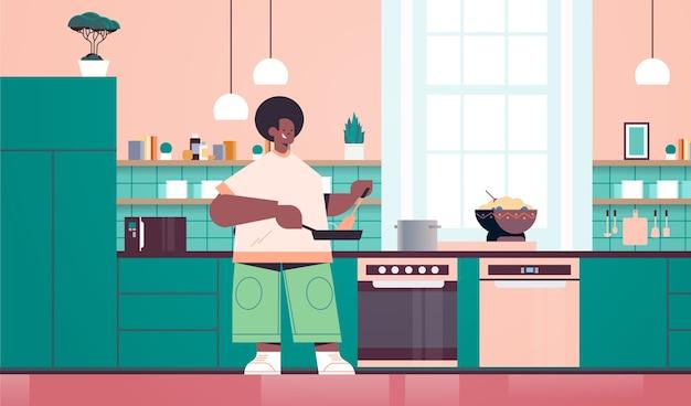 Homem feliz preparando comida saudável em casa, conceito de cozinha moderna interior horizontal