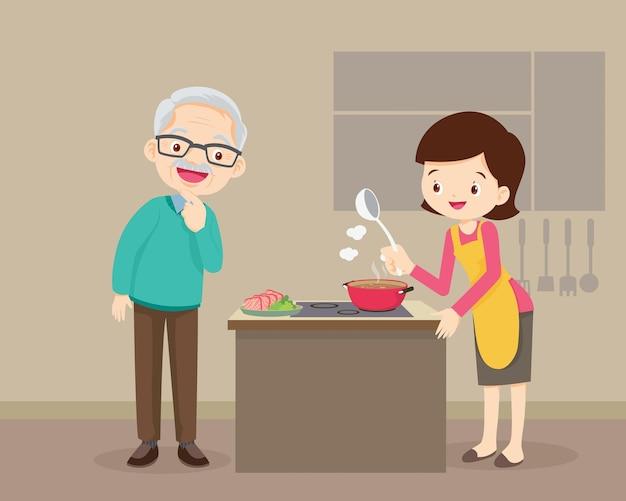 Homem idoso olhando para uma linda mulher cozinhando na cozinha