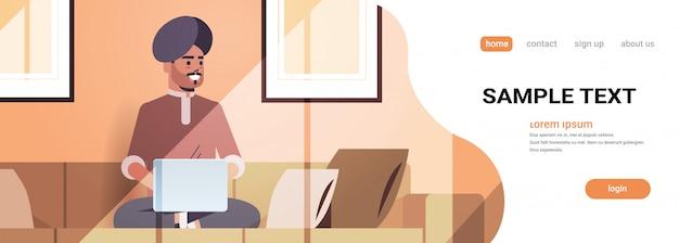 Homem indiano no turbante sentado no sofá usando o laptop cara trabalhando em casa conceito freelance moderna sala de estar interior horizontal comprimento total cópia espaço