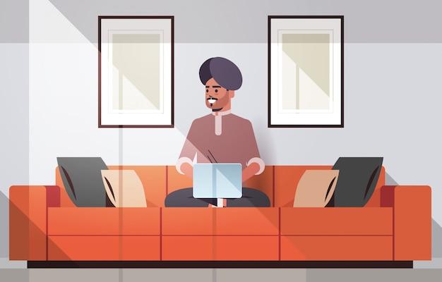 Homem indiano no turbante sentado no sofá usando o laptop cara trabalhando em casa conceito freelance moderna sala interior horizontal comprimento total