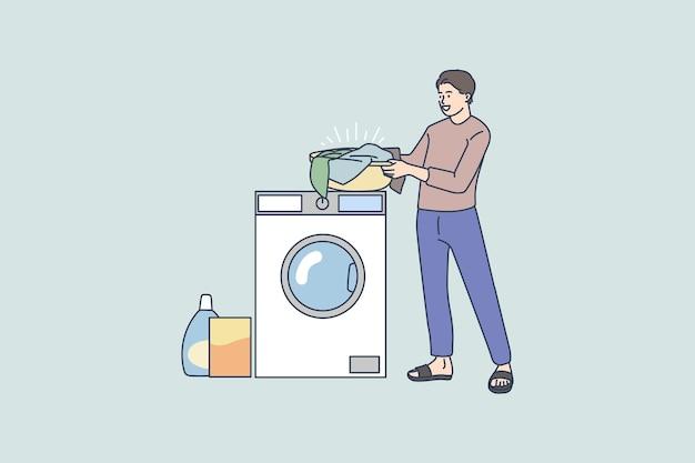 Homem lava roupa e usa máquina de lavar em casa