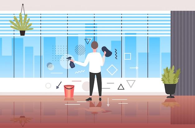 Homem limpador usando pano e spray masculino faxineiro limpeza janelas escritório moderno interior comprimento total desenho horizontal