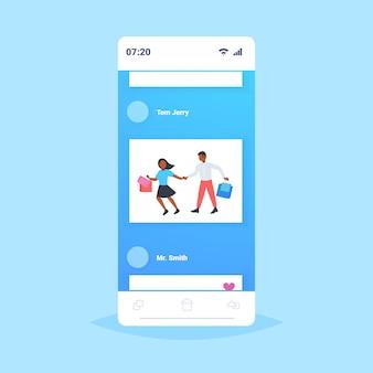 Homem mulher carregando sacolas de compras casal se divertindo caminhando juntos vendas férias loja de varejo consumidor conceito smartphone tela móvel aplicação comprimento total