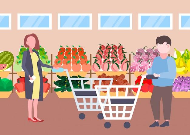 Homem mulher clientes segurando carrinho carrinho comprando frutas orgânicas frescas legumes moderno supermercado shopping interior personagens de desenhos animados comprimento total plana horizontal