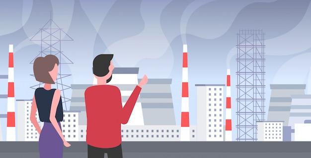 Homem mulher pares olhando planta tubulação desperdício gás tóxico poluição do ar indústria smog poluído conceito povos andar outdoor paisagem industrial retrato horizontal vista traseira