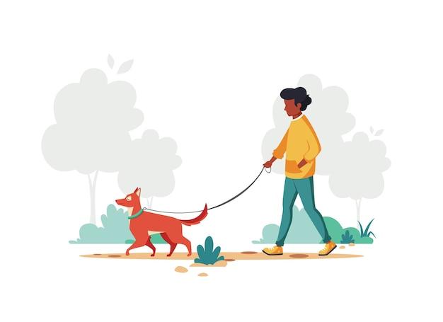 Homem negro andando com o cachorro no parque. atividade ao ar livre