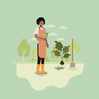 Homem negro plantar árvore no parque com pá