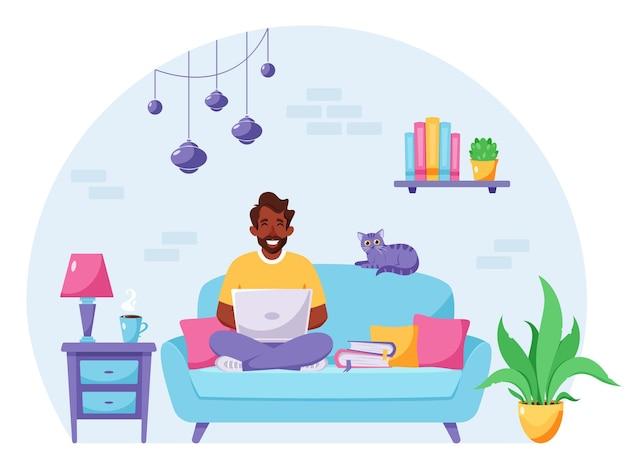 Homem negro sentado em um sofá trabalhando em um laptop. freelancer, escritório doméstico