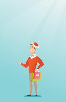 Homem no chapéu de santa que compra presentes do natal.