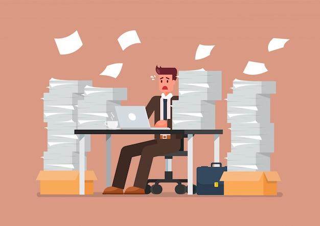 Homem ocupado sobrecarregado, sentado à mesa com o laptop e a pilha de papéis no escritório