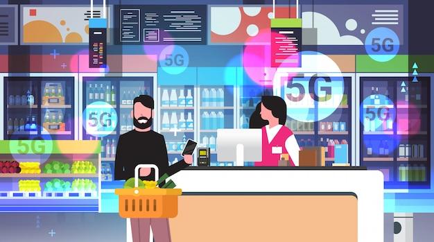 Homem pagando com smartphone no cliente do balcão de check-out usando o sistema de pagamento nfc