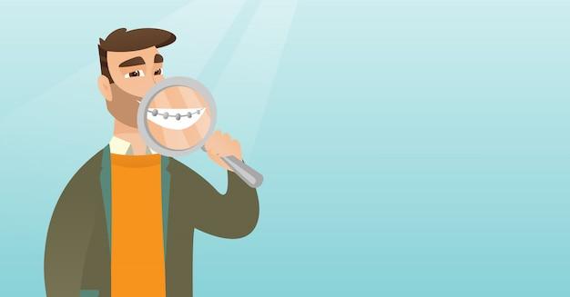 Homem que examina seus dentes com uma lente de aumento.