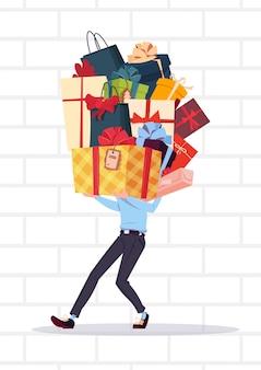Homem que guarda a pilha das caixas de presente sobre o conceito branco dos presentes do feriado do fundo da parede de tijolo