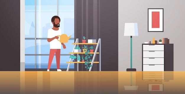 Homem que rega plantas em vaso na cremalheira, segurando a lata de aspersão, fazendo o conceito de serviço doméstico moderno sala de estar interior masculino personagem de desenho animado comprimento total horizontal