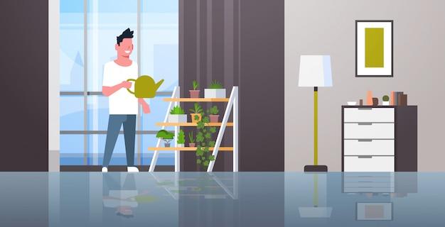 Homem que rega plantas em vaso na cremalheira, sorrindo, segurando a lata de aspersão, fazendo o conceito de trabalho doméstico moderno sala de estar interior masculino personagem de desenho animado