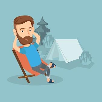 Homem que senta-se na cadeira de dobradura no acampamento.