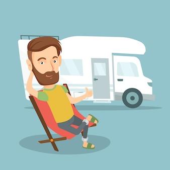 Homem que senta-se na cadeira na frente da camionete de campista.