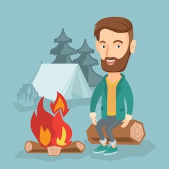 Homem que senta-se no log perto da fogueira no acampamento.