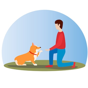 Homem que treina seu cão do corgi de galês. cão fofo feliz. corgi galês. filhote de cachorro se senta e dá pata.