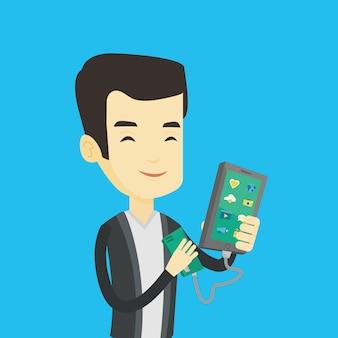 Homem recarregando smartphone da bateria portátil.