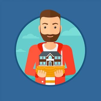 Homem segurando modelo de casa.