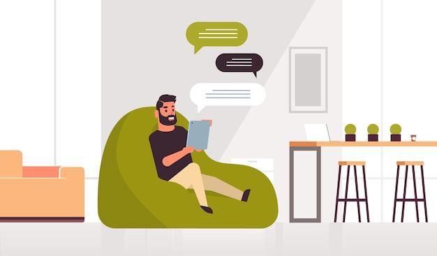 Homem segurando tablet conversando cara de mensagens sentado no saco de feijão usando aplicativo móvel comunicação de bolha de bate-papo da rede social