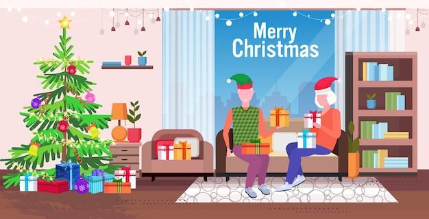 Homem sênior com chapéu de duende dando uma caixa de presente para uma família de mulher madura, sentada no sofá, comemorando o feliz natal feliz ano novo, férias de inverno, conceito moderno, sala de estar