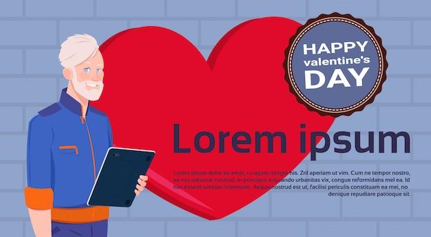 Homem sênior, com, tabuleta, computador, sobre, vermelho, coração modelo, fundo, com, feliz, dia dos namorados, etiqueta