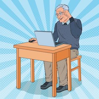 Homem sênior feliz usando laptop