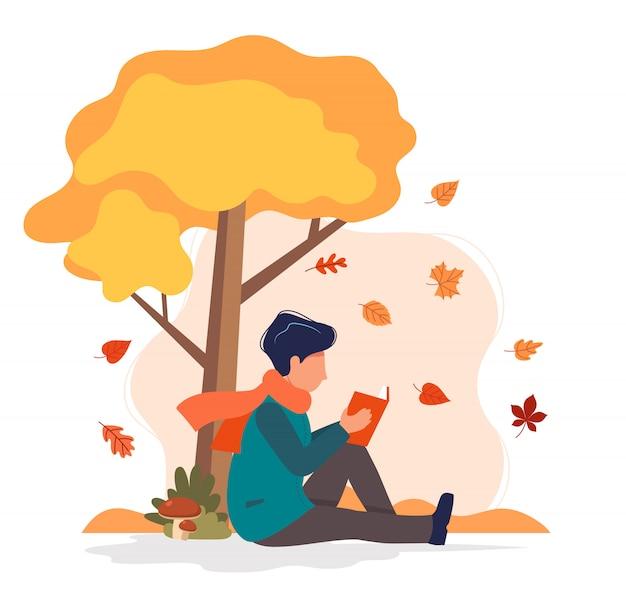 Homem sentado com o livro debaixo da árvore no outono.
