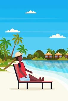 Homem sentado espreguiçadeira espreguiçadeira na ilha tropical villa bungalow hotel praia à beira-mar verde palmas paisagem verão férias plana