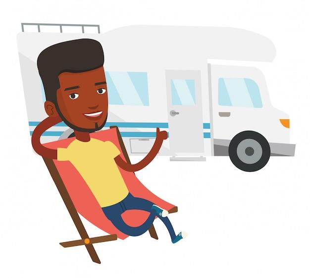 Homem sentado na cadeira em frente a van campista.