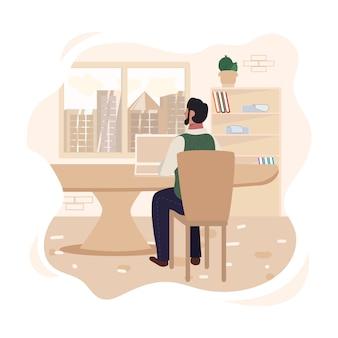 Homem sentado na mesa com o laptop na frente da janela