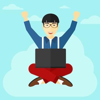 Homem sentado na nuvem com o laptop.