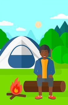 Homem sentado no acampamento.