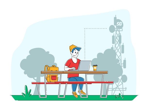 Homem sentado no banco com o laptop na mesa na torre de telecomunicações de transmissão