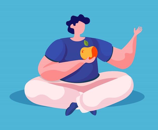 Homem sentado no chão comendo uma maçã grande isolado do sexo masculino no azul