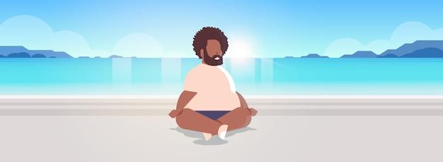 Homem sentado pose de lótus no mar praia relaxar conceito de férias verão seaside oceano bonito