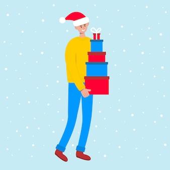 Homem sorridente com chapéu de papai noel carregando uma grande pilha de caixas de presente coloridas se preparando para o natal