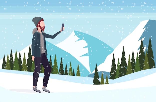 Homem tirando foto de selfie no smartphone câmera casual masculino personagem de desenho animado posando montanhas nevadas paisagem fundo comprimento total