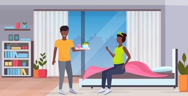 Homem trazendo bandeja de café da manhã com alimentos para mulher grávida sentada na cama família no conceito de gravidez amor moderno quarto em casa interior comprimento total horizontal