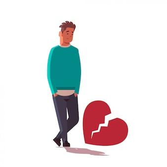 Homem triste com o coração partido de depressão em pé perto de coração partido