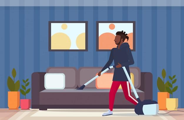 Homem usando aspirador americano africano americano aspirar guy housework serviço serviço housekeeping limpeza moderno conceito sala interior moderno comprimento total