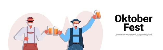 Homens com máscaras médicas segurando canecas de cerveja oktoberfest festa celebração coronavirus conceito de quarentena rapazes com roupas tradicionais alemãs se divertindo com espaço de cópia horizontal